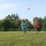 The boys are playing ultimate frisbee in the open field at camp!